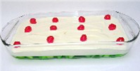 Lime Jello Dessert topped with whipped cream and Maraschino Cherries.