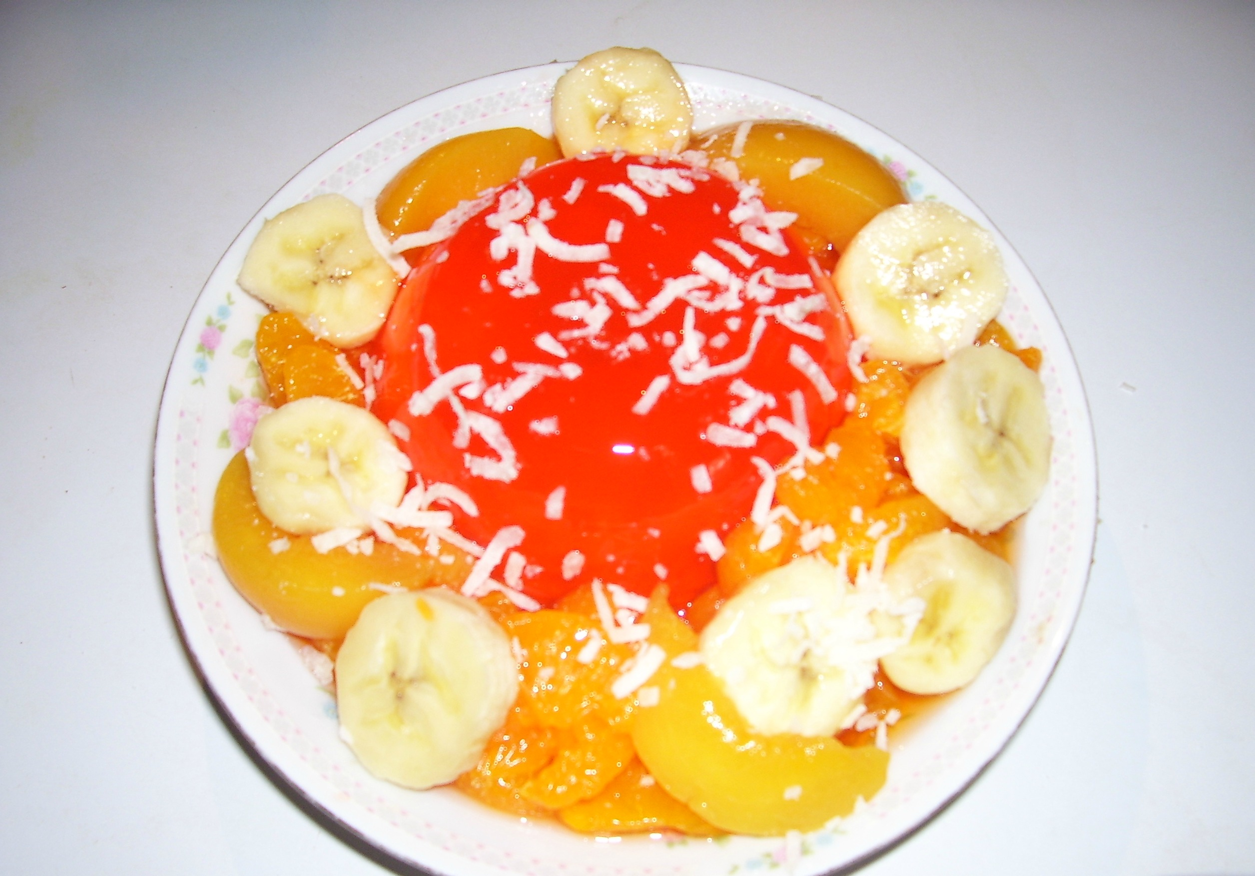 A beautiful and delicious, molded Orange Jello Salad with complimentary fruits atop.