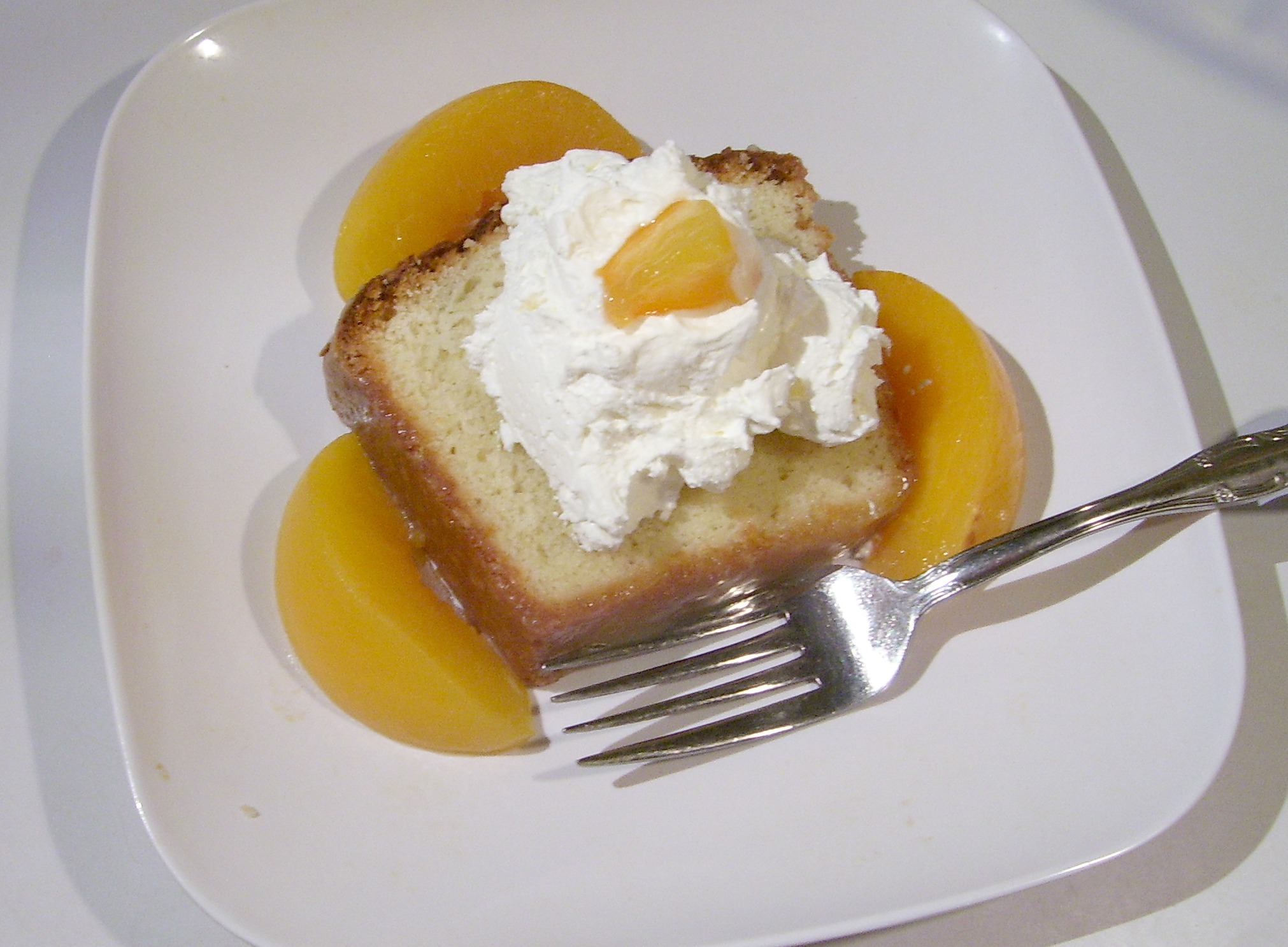 This delicious Old Fashioned Sour Cream Pound Cake made from scratch is served with peaches and sprinkles with Cinnamon Sugar.